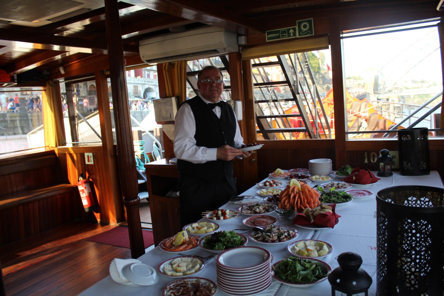 Waiter putting appetizers in Douro cruise with lunch or dinner on board